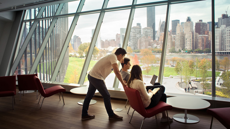 Three founders sit in front of a window at Cornell Tech, overlooking the New York City skyline